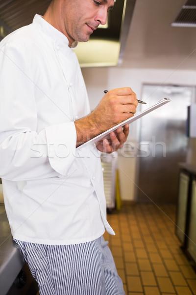 Concentrado masculino cozinhar escrita clipboard cozinha Foto stock © wavebreak_media