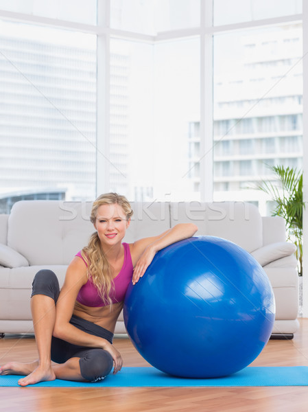 Slim blonde sitting beside exercise ball smiling at camera Stock photo © wavebreak_media