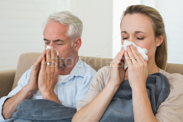 Sick couple blowing their noses sitting on the couch Stock photo © wavebreak_media