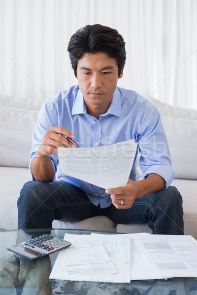 Man sitting on couch working out his finances Stock photo © wavebreak_media