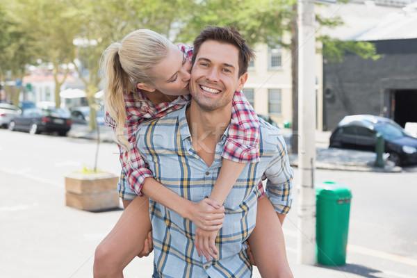 Young hip man giving his blonde girlfriend a piggy back Stock photo © wavebreak_media