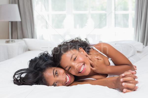 улыбаясь матери дочь позируют вместе кровать Сток-фото © wavebreak_media