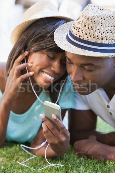 Happy young couple listening to music on the grass Stock photo © wavebreak_media