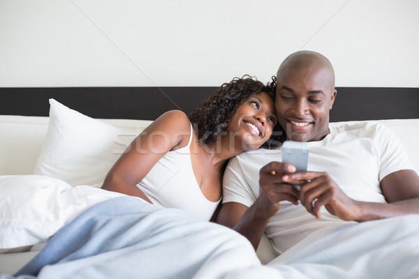 Happy couple cuddling in bed with smartphone Stock photo © wavebreak_media