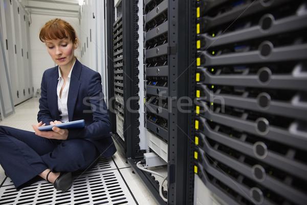 Happy technician sitting on floor beside server tower using tabl Stock photo © wavebreak_media