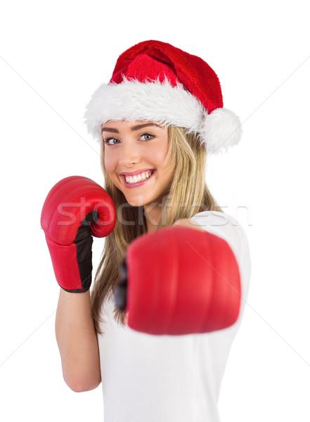 Festive blonde punching with boxing gloves Stock photo © wavebreak_media