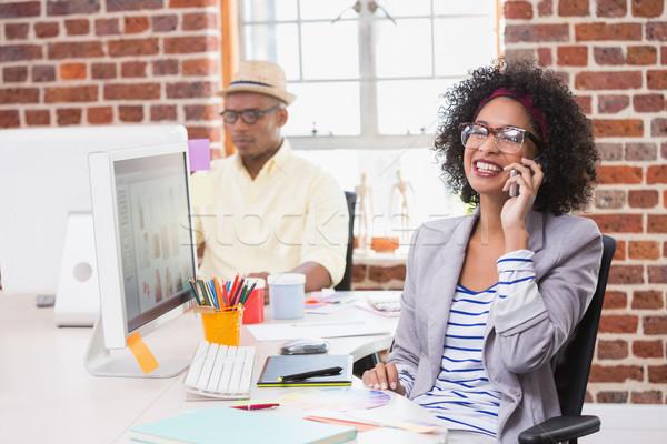 Fotó szerkesztő mobiltelefon iroda mosolyog női Stock fotó © wavebreak_media