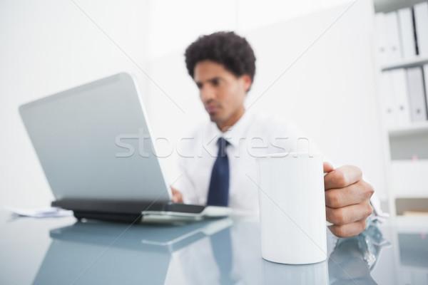 Imprenditore utilizzando il computer portatile mug desk ufficio Foto d'archivio © wavebreak_media
