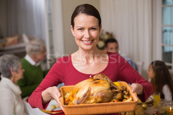 Pretty woman showing the roast turkey in front of her family Stock photo © wavebreak_media