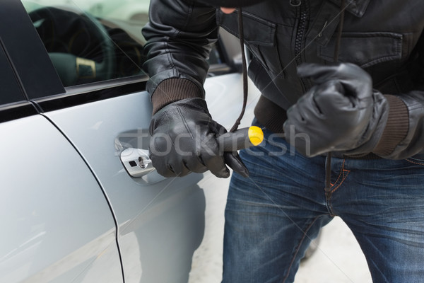 Stock photo: Thief breaking into car with screwdriver