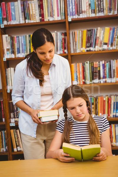 Teacher and girl reading book in library Stock photo © wavebreak_media