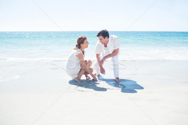 Feliz casal desenho forma de coração areia praia Foto stock © wavebreak_media