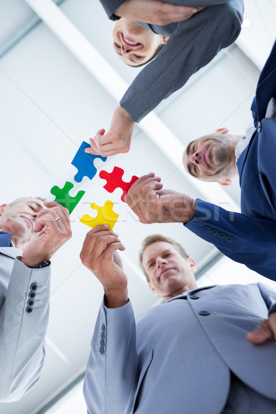 Business colleagues holding piece of puzzle Stock photo © wavebreak_media