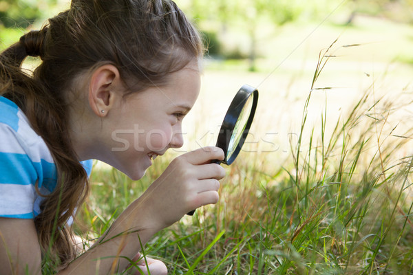 Cute little girl looking through magnifying glass Stock photo © wavebreak_media