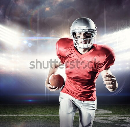 Stock photo: Composite image of portrait of defensive sportsman holding american football