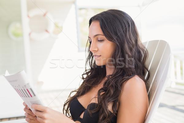 Bastante morena sessão cadeira leitura revista Foto stock © wavebreak_media