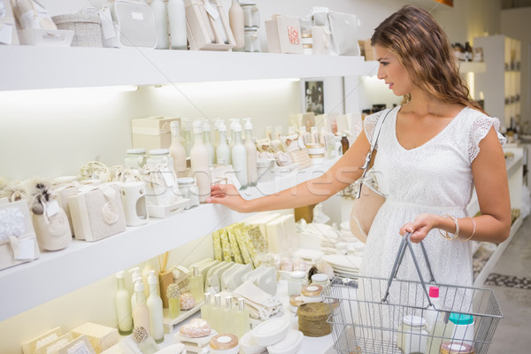 Focused woman with shopping basket browsing products Stock photo © wavebreak_media