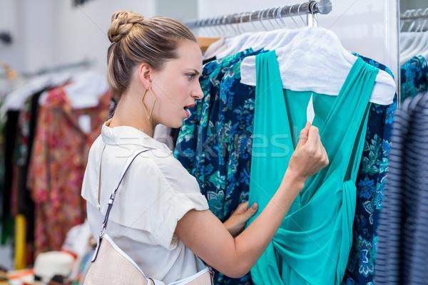 Conmocionado mujer mirando precio etiqueta ropa Foto stock © wavebreak_media