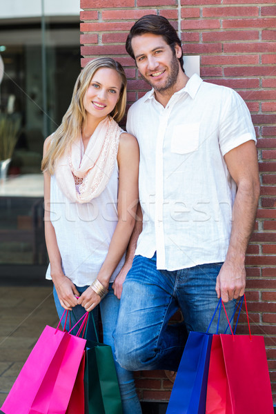 Smiling couple with shopping bags leaning on the wall Stock photo © wavebreak_media