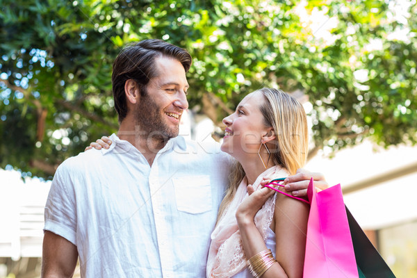 Smiling couple with shopping bags embracing Stock photo © wavebreak_media