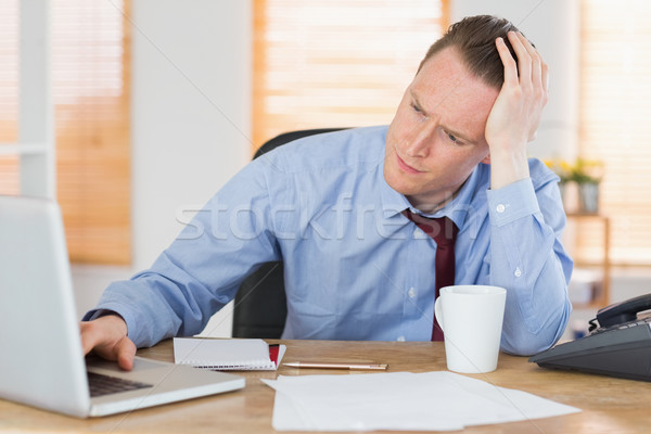 Stressed businessman working at his desk Stock photo © wavebreak_media