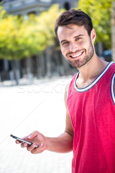 Mosolyog jóképű atléta küldés szöveg portré Stock fotó © wavebreak_media