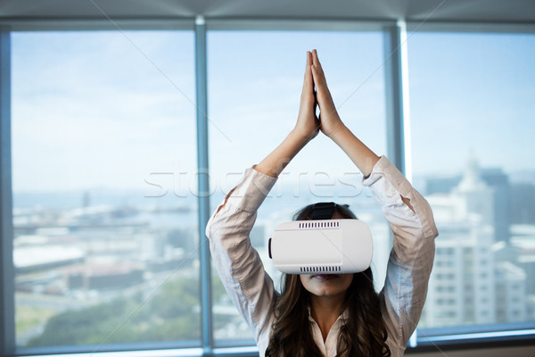 Businesswoman practicing yoga while using virtual reality glasses Stock photo © wavebreak_media