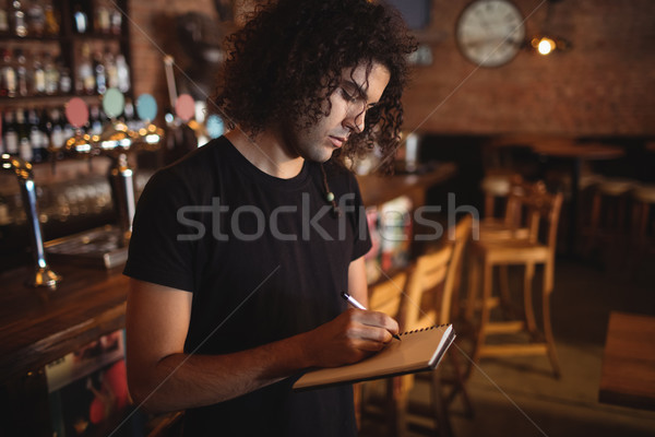 Young barman writing on diary Stock photo © wavebreak_media