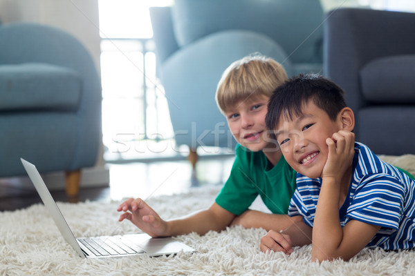 Portrait of siblings lying on rug and using laptop in living room Stock photo © wavebreak_media