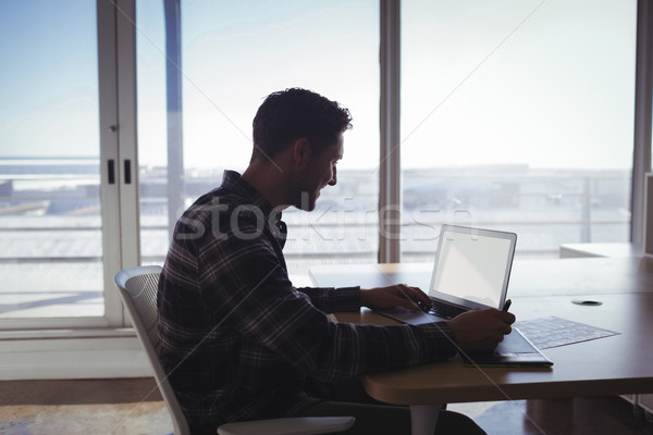Young editor using digitizer and laptop on desk in office Stock photo © wavebreak_media
