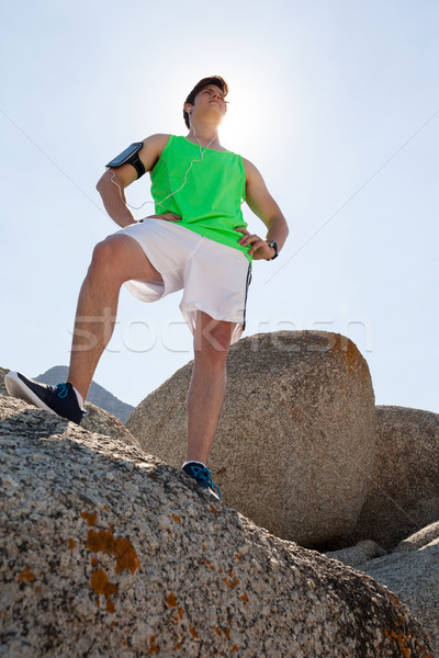 Man standing on rock with hand on hip Stock photo © wavebreak_media