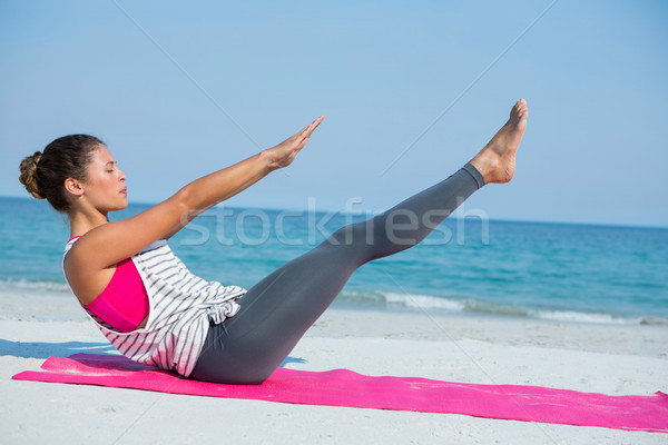 Side view of young woman with eyes closed exercising on mat at beach Stock photo © wavebreak_media