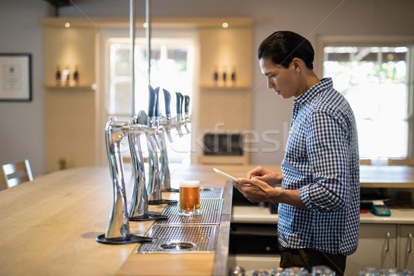 Bar tender using digital tablet at counter Stock photo © wavebreak_media