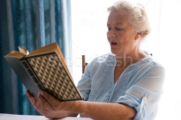 Senior woman reading book while sitting at table Stock photo © wavebreak_media