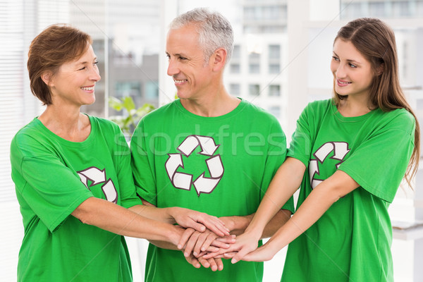Smiling eco-minded colleagues putting hands together Stock photo © wavebreak_media