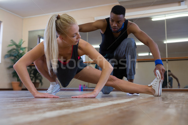 Dancer assisting female friend in stretching on floor Stock photo © wavebreak_media
