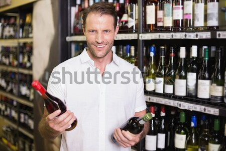 Smiling man holding bottles of wine  Stock photo © wavebreak_media