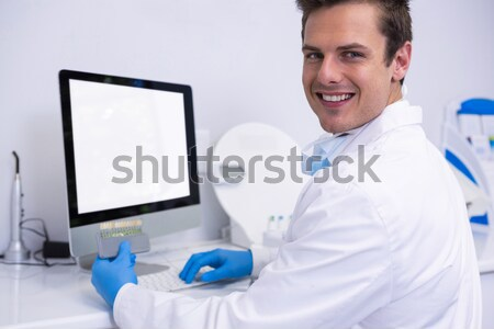 Dentist working while sitting by computer at medical clinic Stock photo © wavebreak_media