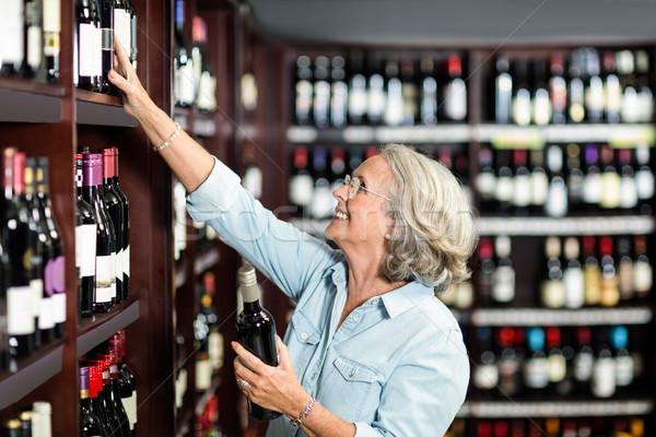 Smiling senior woman choosing wine Stock photo © wavebreak_media