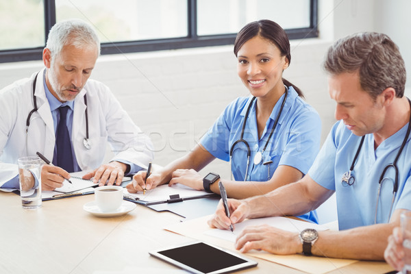 Medical team writing a report in conference room Stock photo © wavebreak_media