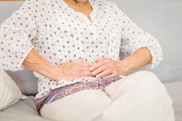 Midsection of senior woman suffering from stomach pain Stock photo © wavebreak_media