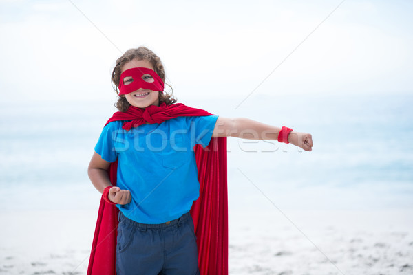 Boy in superhero costume with clenched fist at beach Stock photo © wavebreak_media