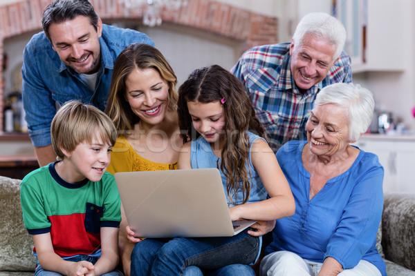 Multi-generation family sitting on sofa and using laptop Stock photo © wavebreak_media
