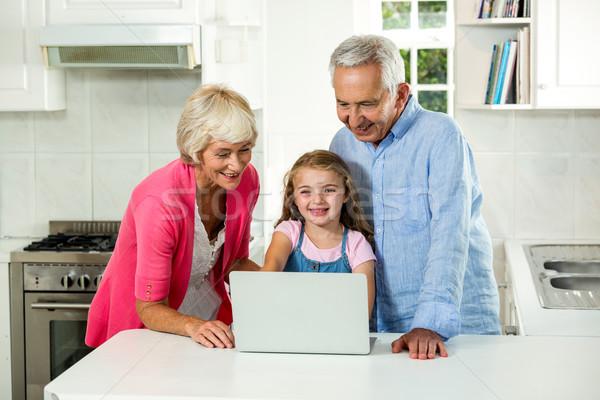 Dedesi kız dizüstü bilgisayar kullanıyorsanız mutfak mutlu ayakta Stok fotoğraf © wavebreak_media