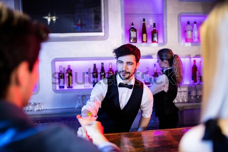 Smiling bartender serving beer to man Stock photo © wavebreak_media