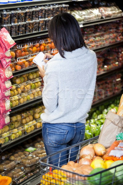 Mujer escrito bloc de notas compras supermercado Foto stock © wavebreak_media