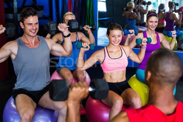 笑みを浮かべて 友達 ダンベル 座って 行使 ストックフォト © wavebreak_media