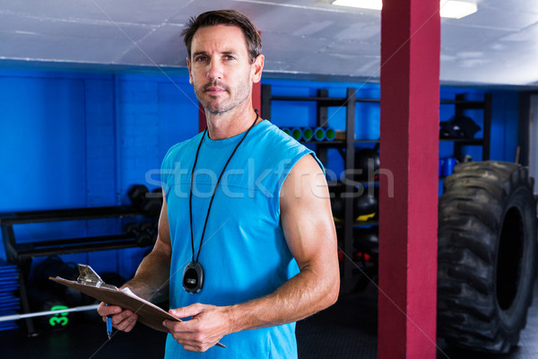 Serious instructor holding clipboard in gym Stock photo © wavebreak_media