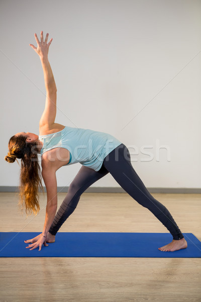 Woman performing triangle pose on exercise mat Stock photo © wavebreak_media