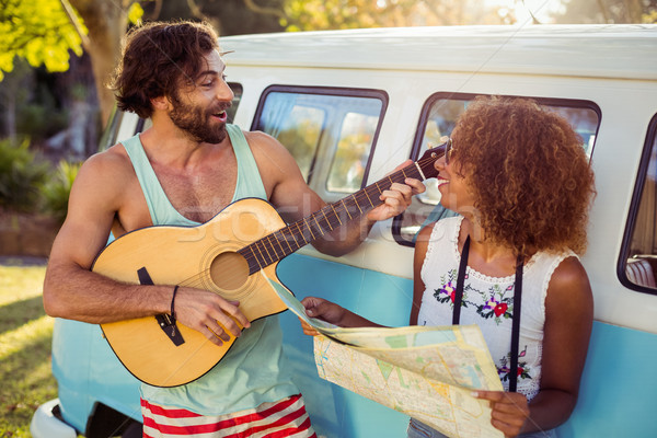 Man playing guitar near campervan and woman holding map beside him Stock photo © wavebreak_media